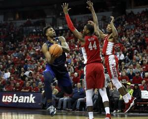 UNR guard Jordan Caroline (24) lays up the ball by ...