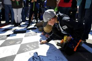 A young fan signs the start finish line before the ...