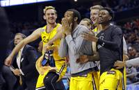 UMBC players celebrate a teammate's basket against Virginia during the second half of a first-round game in the NCAA men's college basketball tournament in Charlotte, N.C., Friday, March 16, 2018.