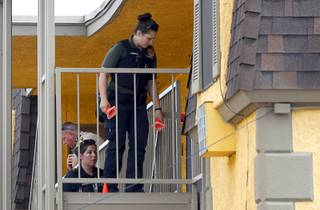 Metro Police crime scene analysts carry evidence cones as they investigate an officer-involved shooting at the Seigal Suites Paradise apartments at Paradise Road and St. Louis Avenue Thursday, March 29, 2018.