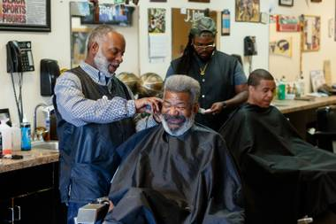 Deandre Sansberry, 48, left, manager and 20 year employee of Blade Masters barbershop, cuts a patrons hair at Blade Masters barbershop, Wednesday, March 29, 2018.