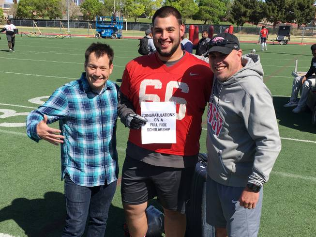 Magician Farrell Dillon, left, from the Masters of Illusion show at Bally's helped UNLV football coach Tony Sanchez, right, present defensive lineman Ammir Aziz a scholarship after practice on Friday, April 13, 2018.