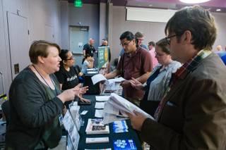 Job seekers look over job application information from the Las Vegas Clark County Library District during the LGBT Career Fair at The Gay & Lesbian Career Center of Southern Nevada, Wednesday, April 4, 2018. The library district offers 6 week courses in a variety of career subjects to anyone with a library card.
