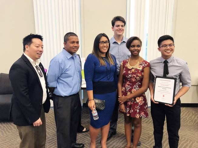 Southeast Career and Technical Academy seniors Deangelo Mortel, 17, Renae Sebastian, 18, and Spencer Ossa, 17, stand with local architects at the AIA Las Vegas High School Design Awards on April 18. The students were awarded $500 for their project, Radiant.