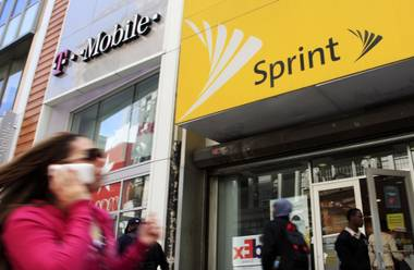FILE- In this April 27, 2010 file photo, a woman using a cell phone walks past T-Mobile and Sprint stores in New York. T-Mobile and Sprint are trying again to combine in a deal that would reshape the U.S. wireless landscape, the companies announced Sunday, April 29, 2018