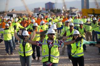 Workers perform bend and stretch exercises before the start of the workday at the Las Vegas Raiders stadium construction site Friday, May 11, 2018. Friday marked the final day of
