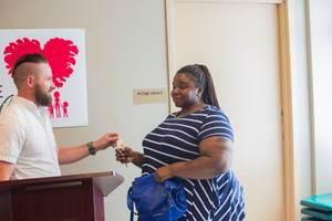 Joel Willden, Director of Yellow-Checker-Star Cab Co, presents  Elizabeth Jacobs with keys to her new car after being selected during a charity event, Friday May 11, 2018.