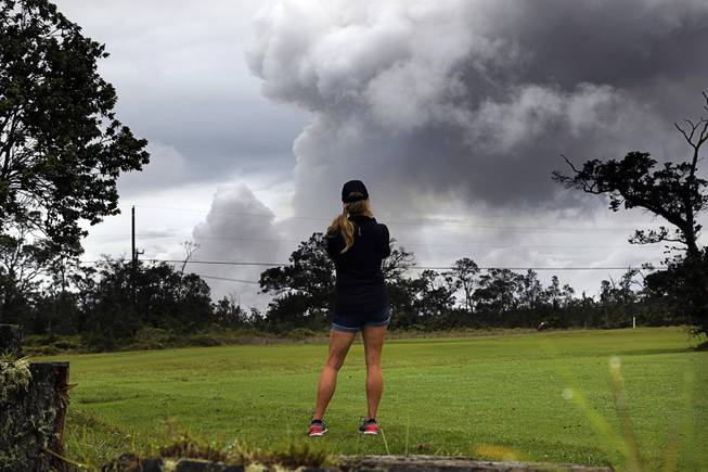 Marie Brant, of Laguna Niguel, Calif., watches as ash rises from the summit crater of Kilauea volcano, Thursday, May 17, 2018, in Volcano, Hawaii. Brant is on vacation in Hawaii. The volcano on Hawaii's Big Island erupted anew Thursday shortly after 4 a.m. with little sound and only modest fury, spewing a steely gray plume of ash about 30,000 feet into the sky that began raining down on a nearby town.