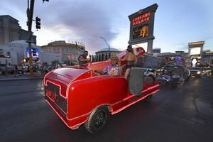 An art car shaped like a stapler drives down the Strip during the