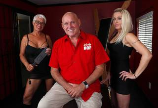 Dennis Hof poses in the Bondage and Discipline Room with Madam on the Menu Sonja Bandolik, left, and legal prostitute Paris Envy at his Love Ranch legal brothel in Crystal, Nev. Tuesday, June 26, 2018. Hof recently won the Republican primary election for Nevada State Assembly District 36.