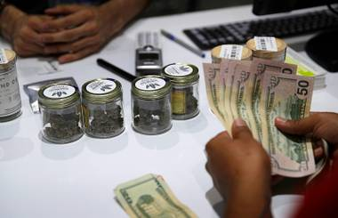 A customer buys marijuana at the Essence cannabis dispensary in Las Vegas, July 1, 2017.