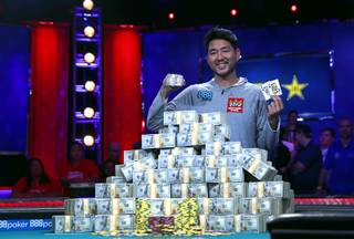 John Cynn holds up his championship bracelet and winning cards after his first place finish in the World Series of Poker Main Event at the Rio Sunday morning, July 15, 2018. Cynn won the bracelet and $8.8 million in prize money.