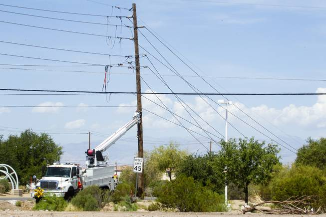 Workers clean up downed power lines on Boulder Highway between Russell and Sunset roads following a thunderstorm the previous night that brought high winds to the area, Friday, July 20, 2018.
