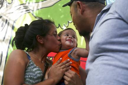 Adalicia Montecino kisses her year-old son Johan Bueso Montecinos, who became a poster child for the U.S. policy of separating immigrants and their children, as Johan touches his father Rolando Bueso Castillo's face, in San Pedro Sula, Honduras, Friday, 20, 2018. Johan Bueso Montecinos arrived in San Pedro Sula and was reunited with his parents on a government bus. Captured by Border Patrol agents in March, Johan's father was deported and the then 10-month-old remained at an Arizona shelter.