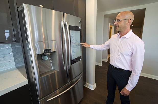 Uri Vaknin, a partner in KRE Capital, writes a digital note on an Internet-enabled Samsung refrigerator in a remodeled condo at the Ogden in downtown Las Vegas Tuesday, Aug. 21, 2018.