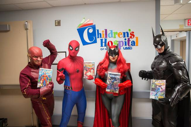 Critical Care Comics' Chase Addison, as The Flash, Michael Mutzhause, as Spider-Man, Lexi Kreuz, as Batwoman, and Tyler Moir, as Batman, pose for a photo at UMC's Children's Hospital as they deliver comic books and toys to kids, Saturday, Aug. 18, 2018.