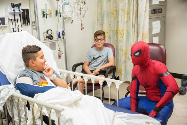 Critical Care Comics' Michael Mutzhause, as Spider-Man, visits with 9-year-old Sami, who is recovering from an elbow injury. He and other friendly superheroes are delivering comic books and toys to kids at UMC's Children's Hospital, Sat Aug. 18, 2018.