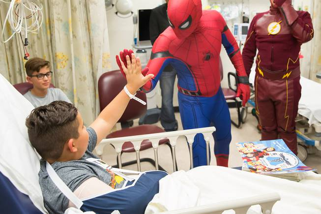 Critical Care Comics' Michael Mutzhause, as Spiderman, gives a high-five to Sami, 9, as he and other friendly superheroes deliver comic books and toys to kids at UMC's Children's Hospital, Saturday, Aug. 18, 2018.