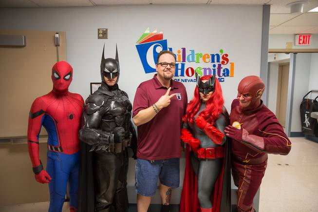 Critical Care Comics'  Michael Mutzhause, as Spiderman, Tyler Moir, as Batman, Jason Golden, founder and president of Critical Care Comics, Lexi Kreuz, as Batwoman, and Chase Addison, as The Flash,  pose for a photo at UMC's Children's Hospital as they deliver comic books and toys to kids, Saturday, Aug. 18, 2018.