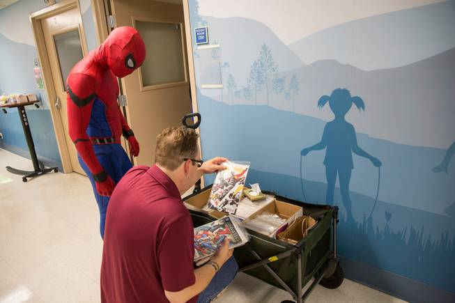 Jason Golden, founder and president of Critical Care Comics, thumbs through various comics as Michael Mutzhause, Spider-Man, prepares to deliver them to a sick child at UMC's Children's Hospital, Sat Aug. 18, 2018.
