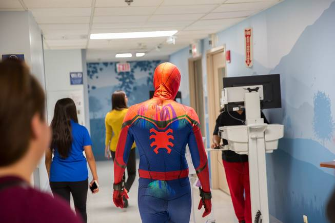 Critical Care Comics' Michael Mutzhause, as Spider-Man, walks dowm a hopital corridor as he and other friendly superheroes deliver comic books and toys to kids at UMC's Children's Hospital, Sat Aug. 18, 2018.