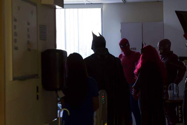 Critical Care Comics' freindly superheroes deliver comic books and toys to a sick child at UMC's Children's Hospital, Sat Aug. 18, 2018.