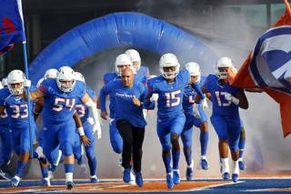 Bishop Gorman Head Coach Kenny Sanchez, center, and players take to the field for a game against Mater Dei at Bishop Gorman Friday, Aug. 24, 2018. Mater Dei (Santa Ana, Calif.) shut out Bishop Gorman 42-0.