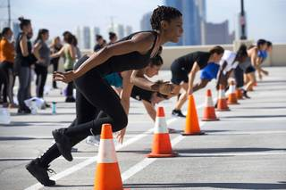 Asia Windley, foreground, and other women run an agility course during a Metro Police Women's Bootcamp on the top floor of the Metro Police parking garage Saturday, Aug. 25, 2018.
