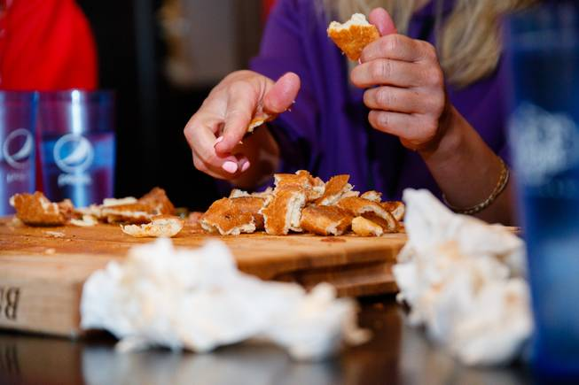 Competitive eater Miki Sudo breaks apart pizza crusts as she attempts Slice of Vegas Double Down Pizza Challenge inside Mandalay Bay, Thursday, Sep. 6, 2018. The challenge, which has never been conquered by any regular customer, consists of eating a 7 pound pizza in under an hour.