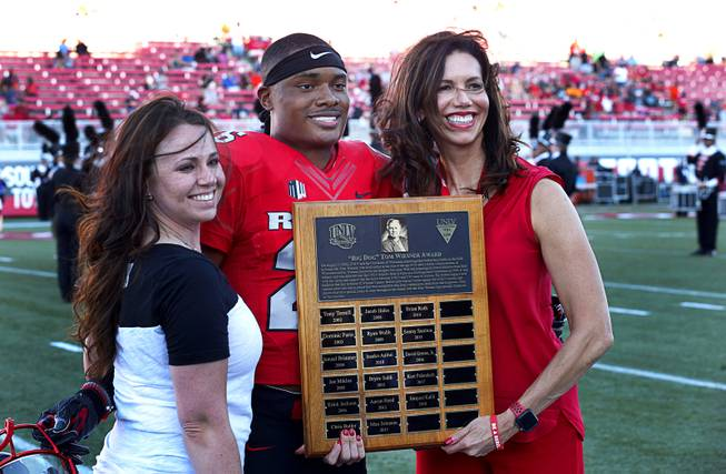 "Amanda Koeller, head brewer for Big Dogs, and UNLV Athletic Director Desiree Reed-Francois, presents the ""Big Dog"" Tom Wiesner Award to defensive back Jocquez Kalili before a game against UTEP at Sam Boyd Stadium Saturday, Sept. 8, 2018. The award is given given to UNLV football players who have Wiesner's ""courage, enthusiasm, dedication and toughness."""