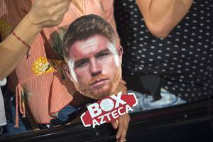 A boxing fan holds a photo of middleweight boxer Canelo Alvarez of Mexico as she waits for boxers to make their arrivals the MGM Grand hotel-casino in Las Vegas, Nev. Tuesday, Sept. 11, 2018.