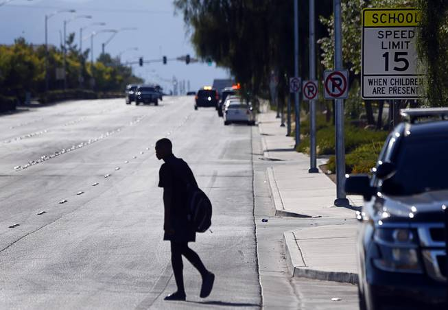 A student crosses Alexander Road after a shooting at Canyon Springs High School in North Las Vegas Tuesday, Sept. 11, 2018. One person was killed.