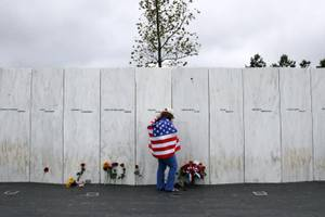Chrissy Bortz of Latrobe, Pa., pays her respects at the Wall of Names at the Flight 93 National Memorial in Shanksville, Pa. after a Service of Remembrance Tuesday, Sept. 11, 2018, as the nation marks the 17th anniversary of the Sept. 11, 2001 attacks. The Wall of Names honor the 40 people killed in the crash of Flight 93. (AP Photo/Gene J. Puskar)