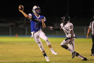 Moapa Valley quarter back Luke Bennett (5) throws the ball under pressure from Cheyenne player Ryan Buchanan (24) during a game at Moapa Valley High School, Friday, Sep. 14, 2018.