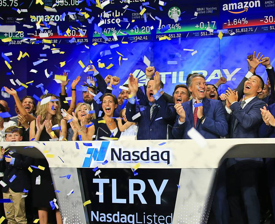 In this July 19, 2018, file photo Brendan Kennedy, third from right in front, CEO and founder of British Columbia-based Tilray Inc., a major Canadian marijuana grower, leads cheers as confetti falls to celebrate his company's IPO (TLRY) at Nasdaq in New York. Investors are craving marijuana stocks as Canada prepares to legalize pot next month, leading to giant gains for Canada-based companies listed on U.S. exchanges.