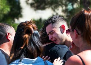 A mourner is consoled as he cries at the Liberty At Paradise Community in Henderson Saturday Sept. 22. He and others were there for a ceremony honoring Selina Rowsell, her son, Arias, and his younger brother, Avi. The three were slain Sept. 20 in the same community by a perpetrator who then took his life