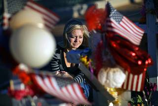 Alexandra Gurr cries as she lays flowers at a makeshift memorial for victims of a mass shooting Monday, Oct. 9, 2017, in Las Vegas. Stephen Paddock opened fire on an outdoor country music concert.