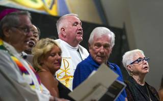 Father Bob Stoeckig, center, is joined by religious leaders on the Altar as they sing 'let There Be Peace on Earth