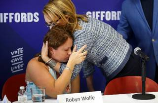 Robyn Wolfe, an Oct. 1 shooting survivor whose husband Bill Wolfe Jr. was killed, is embraced by former Arizona Congresswoman Gabrielle