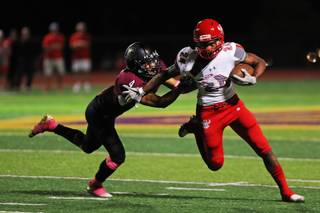 Arbor View running back Daniel Mitchell (24) runs the ball as Faith Lutheran player Sebastian Burke (4) attempts to tackle him during a game at Faith Lutheran High School, Friday, Oct. 5, 2018.
