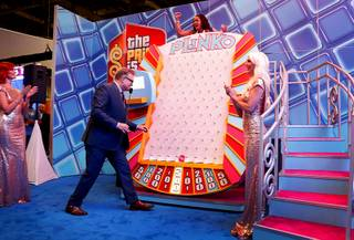 Isidra Randal, a Venetian guest services representative, celebrates as she wins a Plinko game with Drew Carey, host of