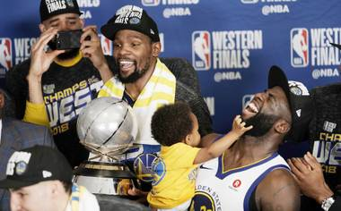 Golden State Warriors forward Kevin Durant holds the trophy as he and teammate Draymond Green, right, celebrate with teammates after defeating the Houston Rockets in Game 7 of the NBA basketball Western Conference finals May 28 in Houston.