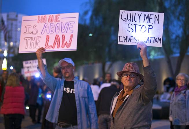 Aaron Caldwell, left, and Brian Sherrett hold up signs during a protest in front of the Lloyd D. George Federal Building in downtown Las Vegas Thursday, Nov. 8, 2018. Following the firing of U.S. Attorney General Jeff Sessions, activists are asking that the investigation into alleged Russian interference in the 2016 elections is protected.