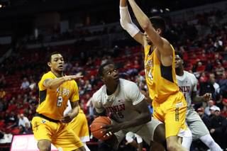 UNLV Rebels forward Cheickna Dembele (15) looks to make a lay up under pressure from Valparaiso Crusader defenders Deion Lavender (2) and Jaume Sorolla (14) during a game at the Thomas & Mack Center Wednesday, Nov. 28, 2018.