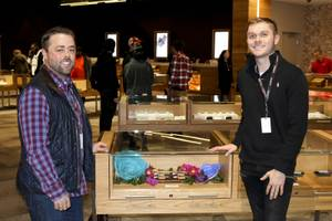 Hunter & Leaf founders Jacob Silverstein (left) and Zachary LoBello (right) pose in front of a display case of their products at Planet 13 dispensary on December 3, 2018