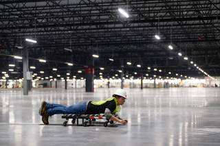 Kameron Lurf lays stickers to guide sorting robots during a tour of a new 855,000- square-foot Amazon customer fulfillment facility, in North Las Vegas Thursday, Dec. 6, 2018. This is Amazon's sixth fulfillment center in Nevada and will create over 1,000 full-time jobs when completed.