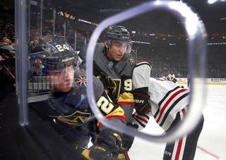 Vegas Golden Knights center Oscar Lindberg (24) and left wing Tomas Nosek (92) fight for the puck with Chicago Blackhawks defenseman Jan Rutta (44) during a game against the Chicago Blackhawks at T-Mobile Arena Thursday, Dec. 6, 2018.