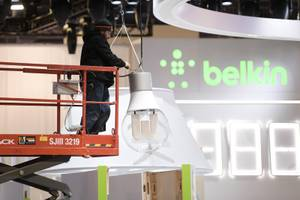 A worker hooks up an oversized light bulb during setup for CES Saturday, January 5, 2019, at the Las Vegas Convention Center.
