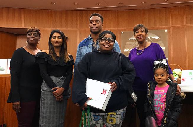 Barbara Marshall, from left, Shenali Rajaratnam, the founder of ShopNowToFund, Brandon Marshall and North Las Vegas Mayor Pro Tem Pamela Goynes-Brown stand with one of the families who received a FEEL box at North Las Vegas City Hall on Thursday, Jan. 10, 2019.