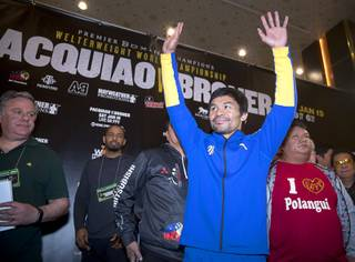 WBA welterweight champion Manny Pacquiao of the Philippines waves to fans in the MGM Grand  lobby during his